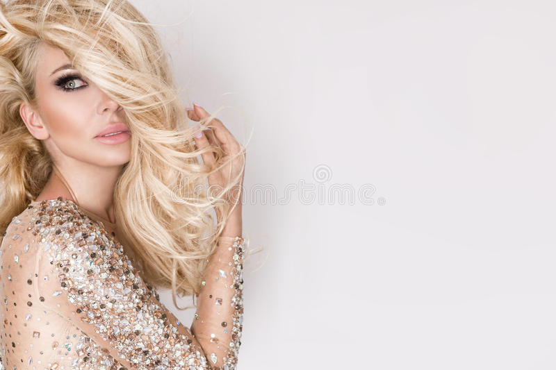 Portrait of the beautiful blonde with amazing eyes, dense long hair with highlights. Green eyes and sensory perfect face dressed in transparent dress with stock images