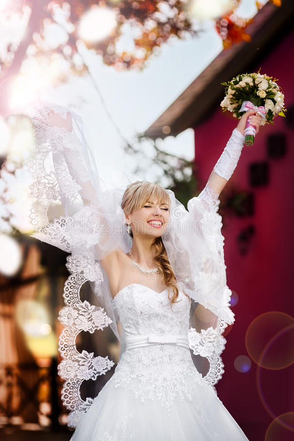 Portrait of a beautiful blonde bride with wedding bouqet. In the hand stock image