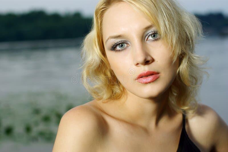 Portrait of beautiful blonde girl. On blue sky stock photos