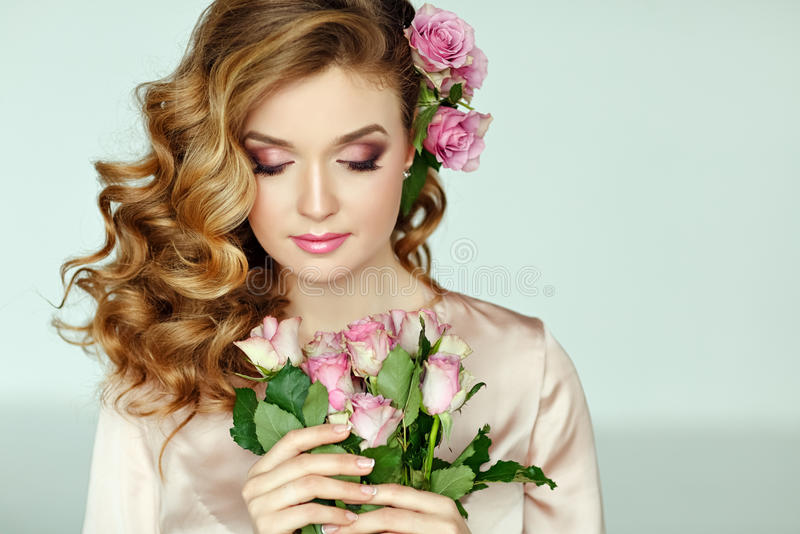 Portrait of a beautiful blonde girl with delicate pink roses on royalty free stock photo