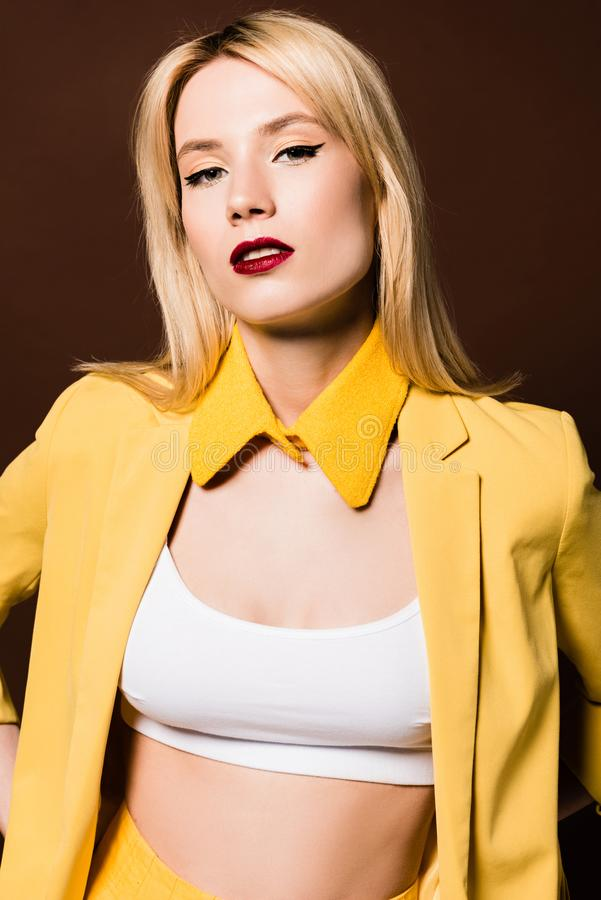 Portrait of beautiful blonde girl in fashionable yellow clothes looking at camera. Isolated on brown royalty free stock photography