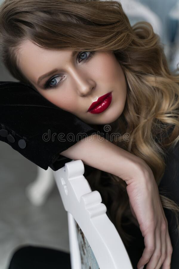 Portrait of a beautiful blonde girl with red lips and evening make-up, wavy hair wearing a black velvet jacket, sitting, leaning stock image
