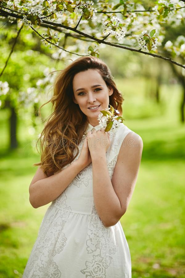 Portrait of beautiful blonde girl in white dress near a flowering tree in park royalty free stock image