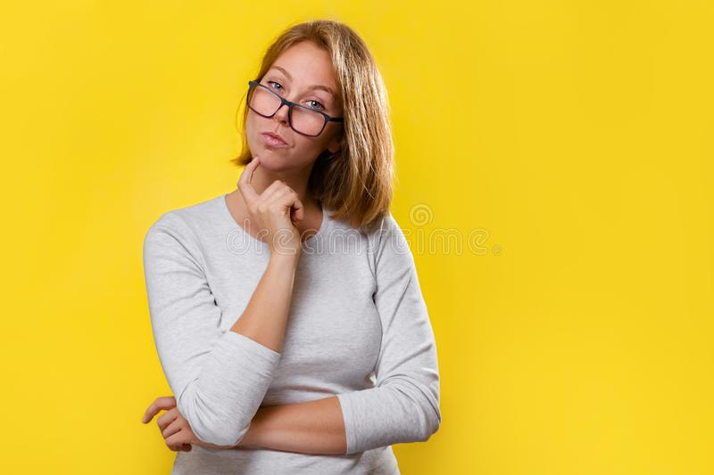 Portrait of a beautiful blonde with glasses, who looks thoughtfully. Yellow background royalty free stock photo