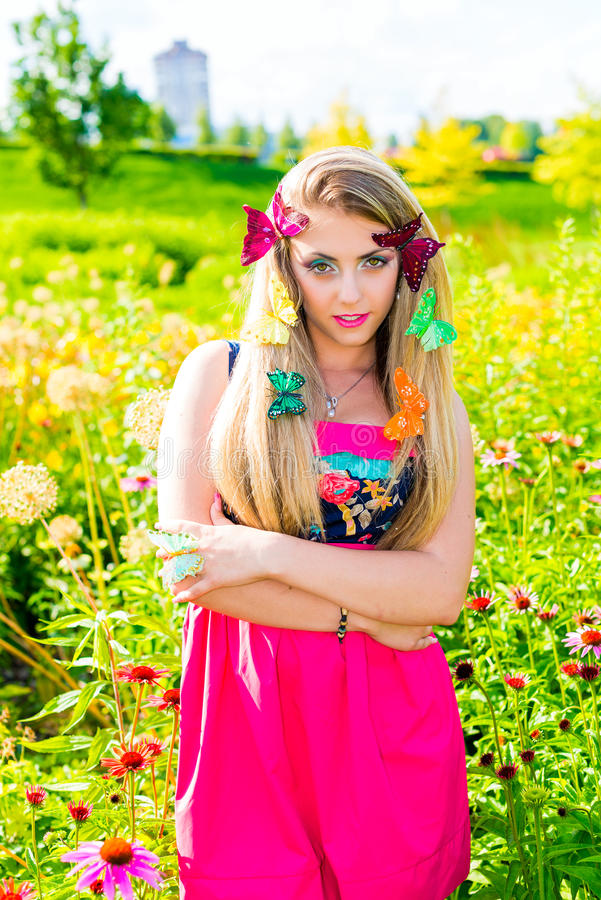 Portrait of beautiful blonde with green eyes. With flowers and butterfly in her hair stock image
