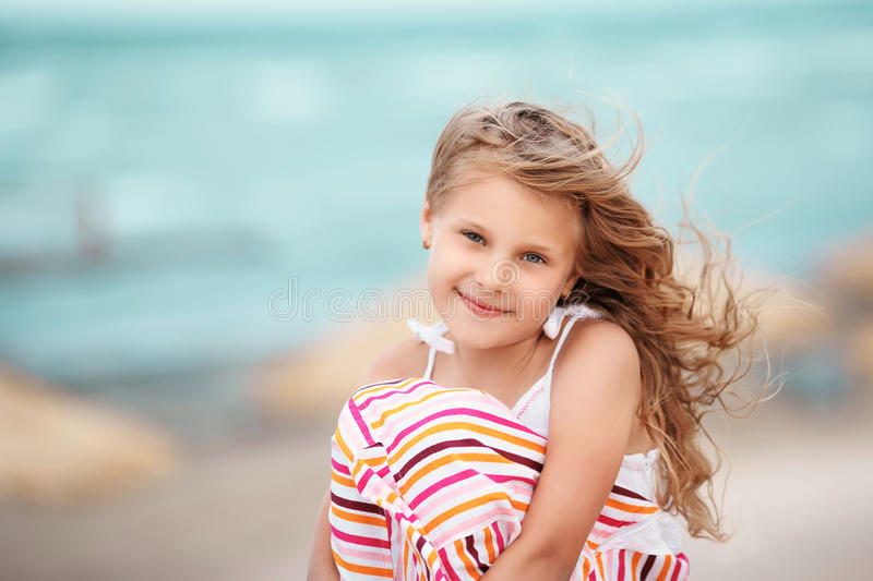 Portrait of a beautiful blonde little girl on the beach at a tropical resort. royalty free stock images