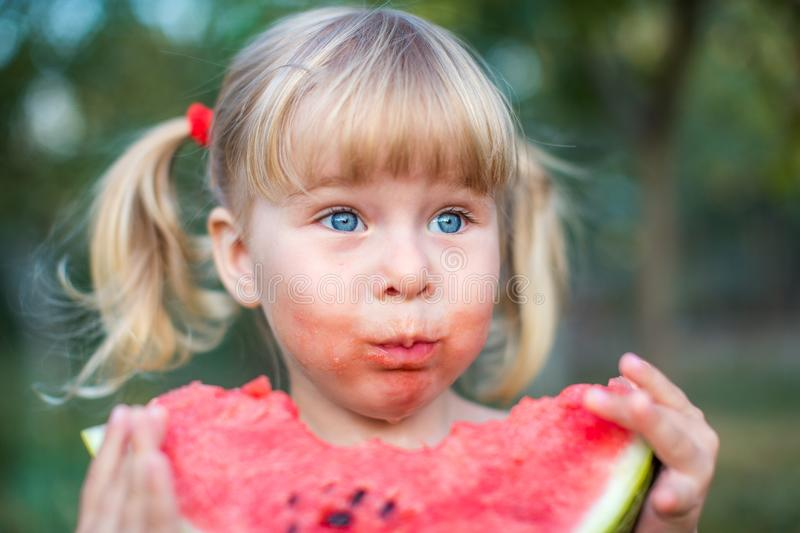 Portrait of beautiful blonde little girl with two ponytails eating watermelon royalty free stock photography