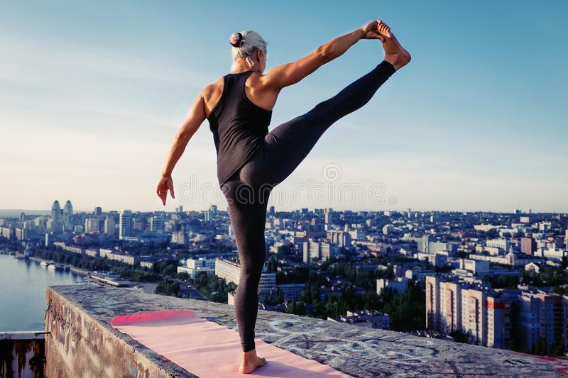 Portrait of beautiful blonde strong woman in sportwear doing workout stretching on the roof of a skyscraper above the big city at royalty free stock images