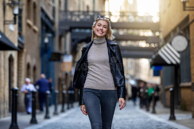 Portrait of a beautiful, blonde urban woman walking in the city stock images