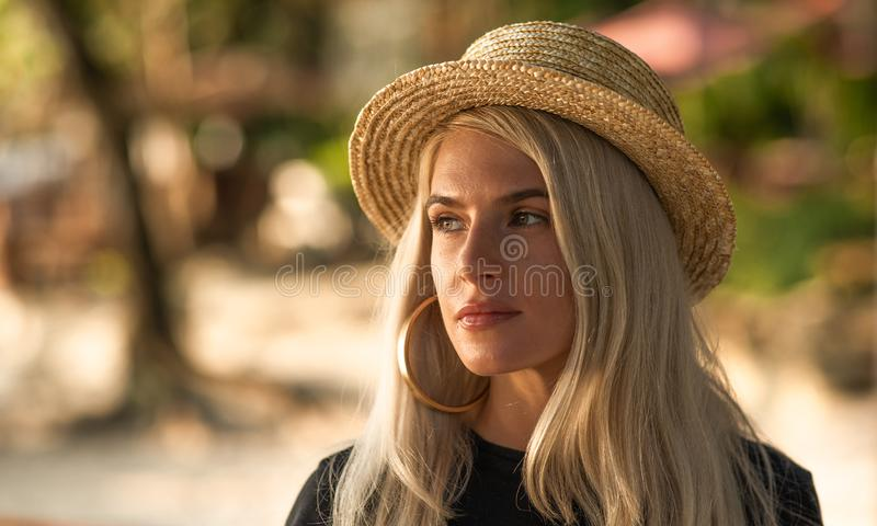 Portrait of a beautiful blonde wearing a straw hat. Modern woman. Travel around the world royalty free stock photo