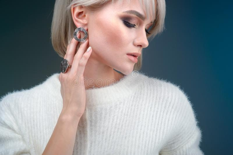 Portrait of a beautiful blonde woman with a beautiful ring and earrings posing in the studio on a blue background. The Portrait of a beautiful blonde woman with stock image