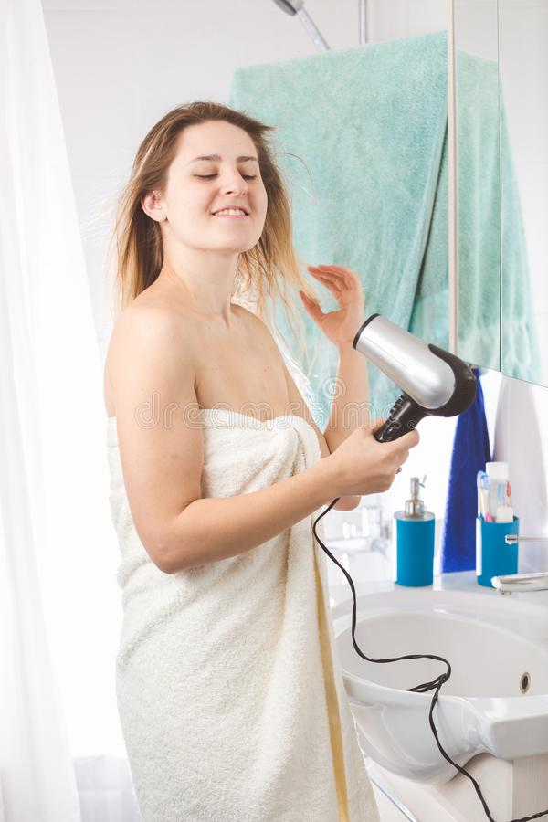 Portrait of beautiful blonde woman drying long hair with hairdryer royalty free stock photo