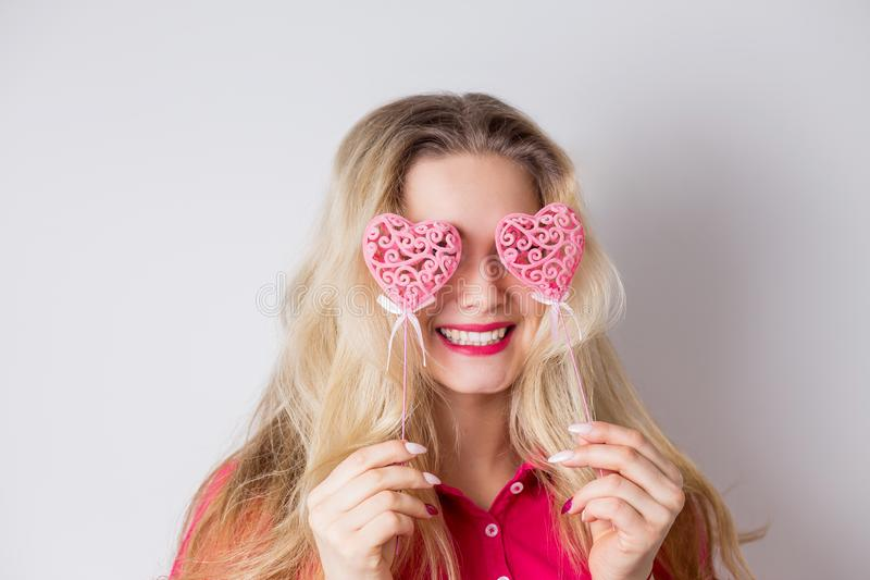 Portrait of beautiful blonde woman holding two pink heart on white background stock image