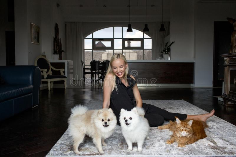 Portrait of a beautiful blonde woman in the interior with animals royalty free stock photo
