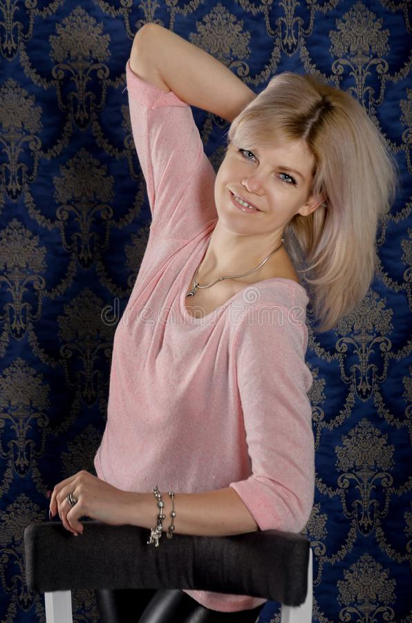 Portrait of a beautiful blonde woman in a pink jacket and leather pants in a classic interior with blue wallpaper with monograms stock images