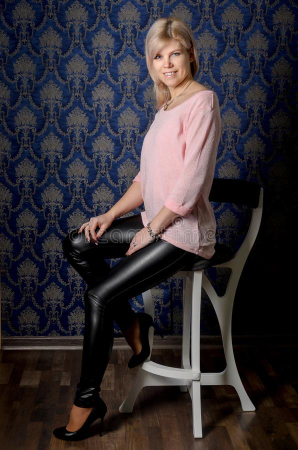 Portrait of a beautiful blonde woman in a pink jacket and leather pants in a classic interior with blue wallpaper with monograms royalty free stock photo