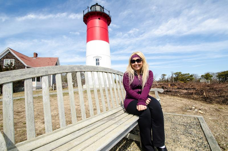 Portrait of a beautiful blonde woman sitting on a bench in front of Nauset Lighthouse on Cape Cod stock images