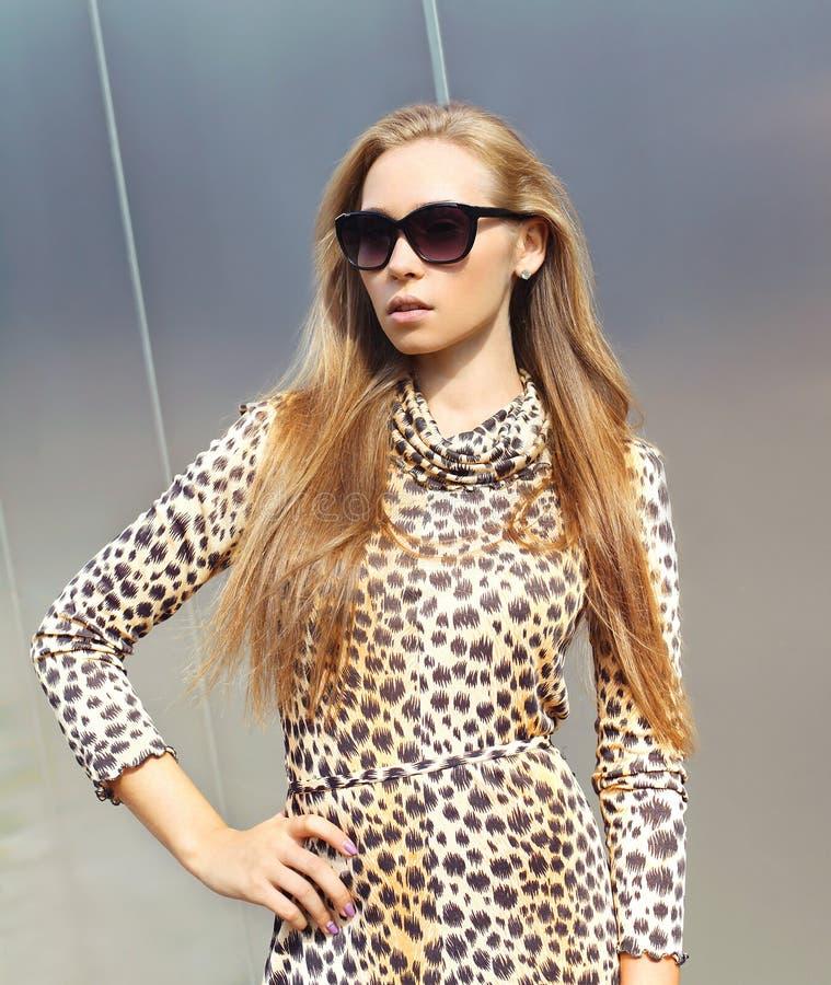 Portrait of beautiful blonde woman wearing a leopard dress stock image