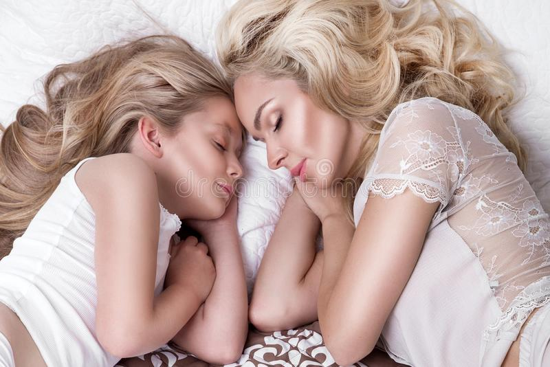 Portrait of the beautiful blonde woman mother and daughter on the beautiful face and amazing eyes lie sleeping on a bed in an eleg royalty free stock image