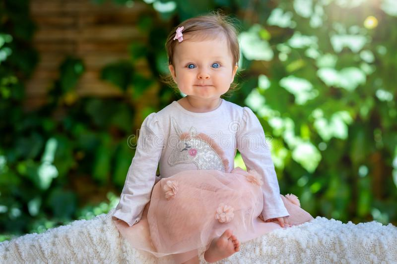 Portrait of a beautiful, blue eyed baby girl in a park stock photography