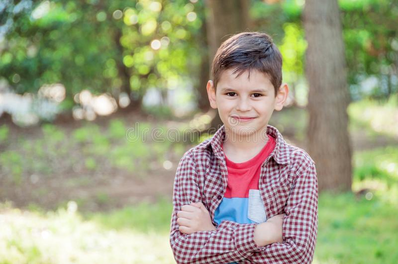 Portrait of a beautiful boy in the park, standing with arms crossed and smiling. Adorable young happy boy. royalty free stock photos