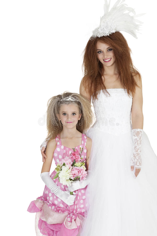 Portrait of beautiful bride and bridesmaid holding flower bouquet over white background