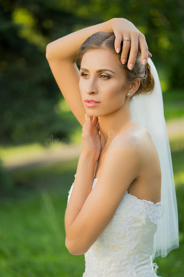 Portrait of a beautiful bride in the park royalty free stock photos