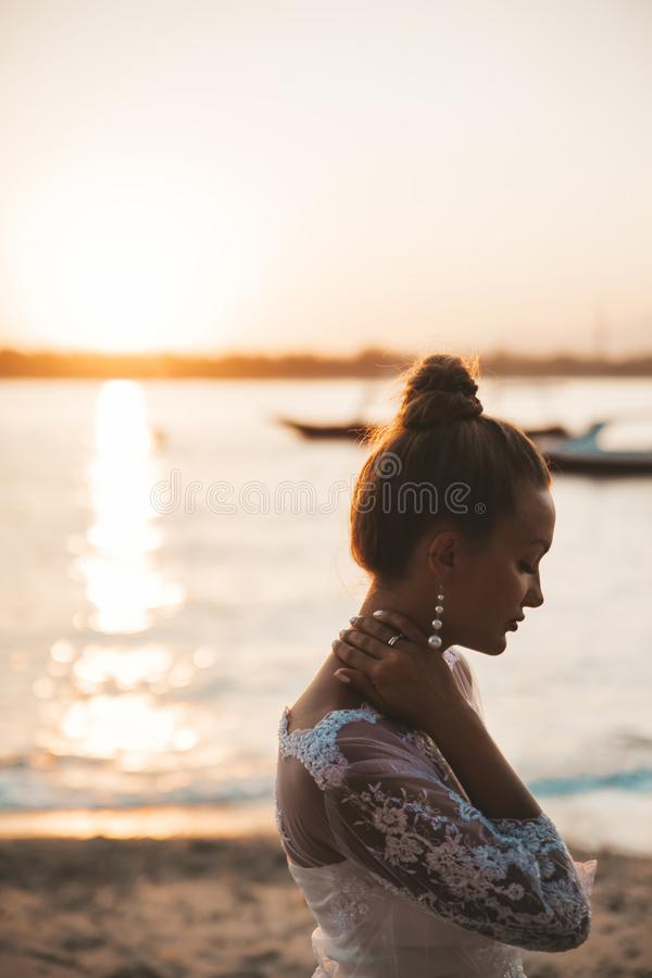 Beautiful bride posing on the beach behind sea at sunset stock photos