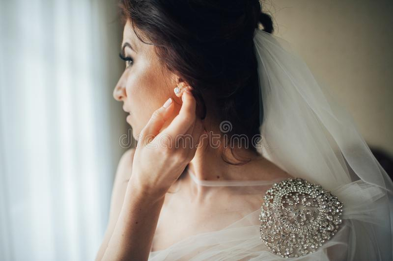 Portrait of the beautiful bride in the white dress in hotel room royalty free stock photo