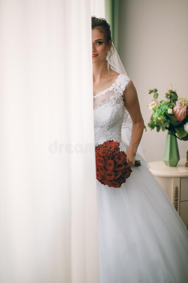 Portrait of beautiful bride in white silk dressing gown with curly hairstyle and long veil standing near window in bedroom stock photo