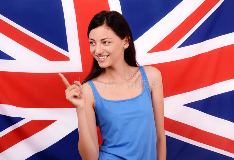Portrait of a beautiful British girl smiling and pointing to the side.