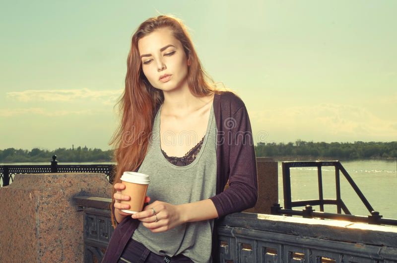 Portrait of beautiful brown haired teen girl standing and looking down. She keeping takeaway drink. Urban city scene royalty free stock photography