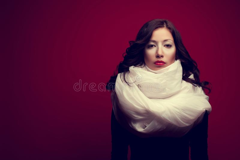 Portrait of a beautiful brunette with arty makeup wearing a vapory white silk scarf looking like cream stock photos