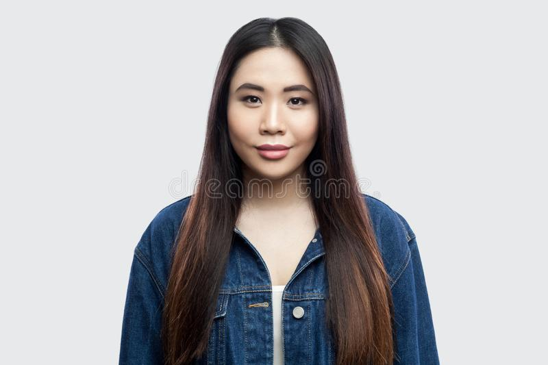 Portrait of beautiful brunette asian young woman in casual blue denim jacket with makeup standing, smiling and looking at camera royalty free stock images