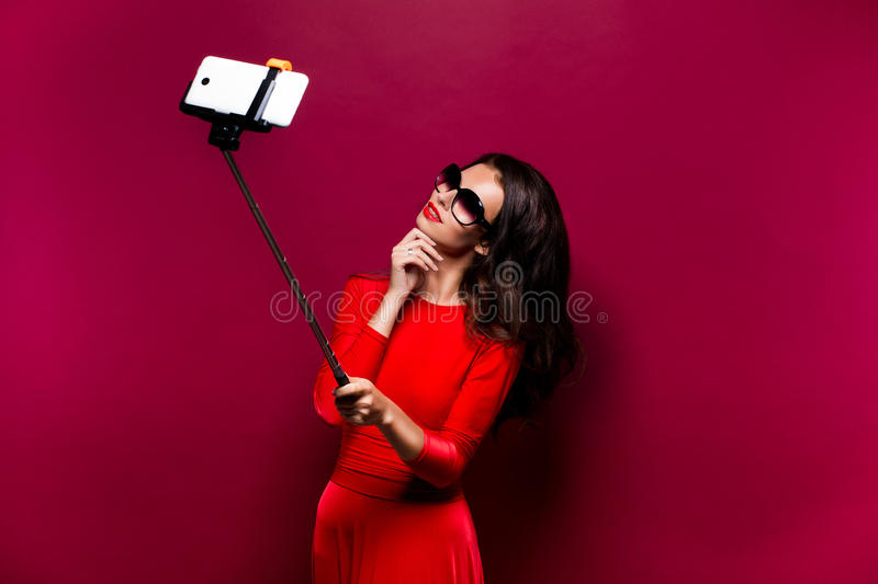 Portrait of beautiful brunette in awesome dress and red lips wearing sunglasses while making selfie with stick. royalty free stock photo