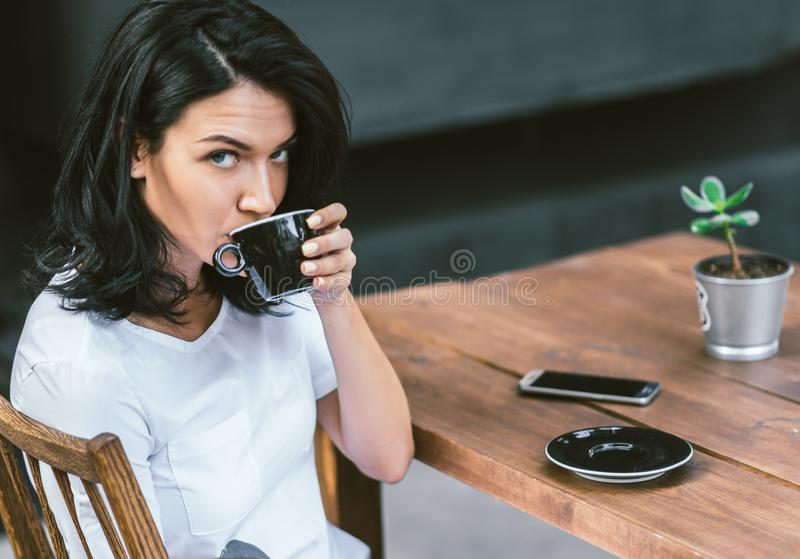 Portrait of beautiful brunette Caucasian holding mug with coffee and enjoying nice weather relaxing alone in modern coffee shop at royalty free stock photos