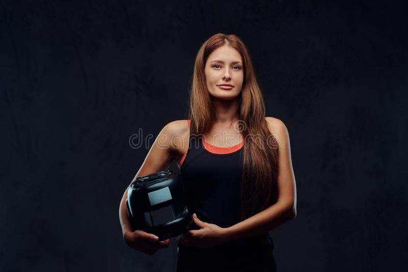 Portrait of a beautiful brunette female boxer in sportswear holds a protective helmet, looking at a camera. on stock image