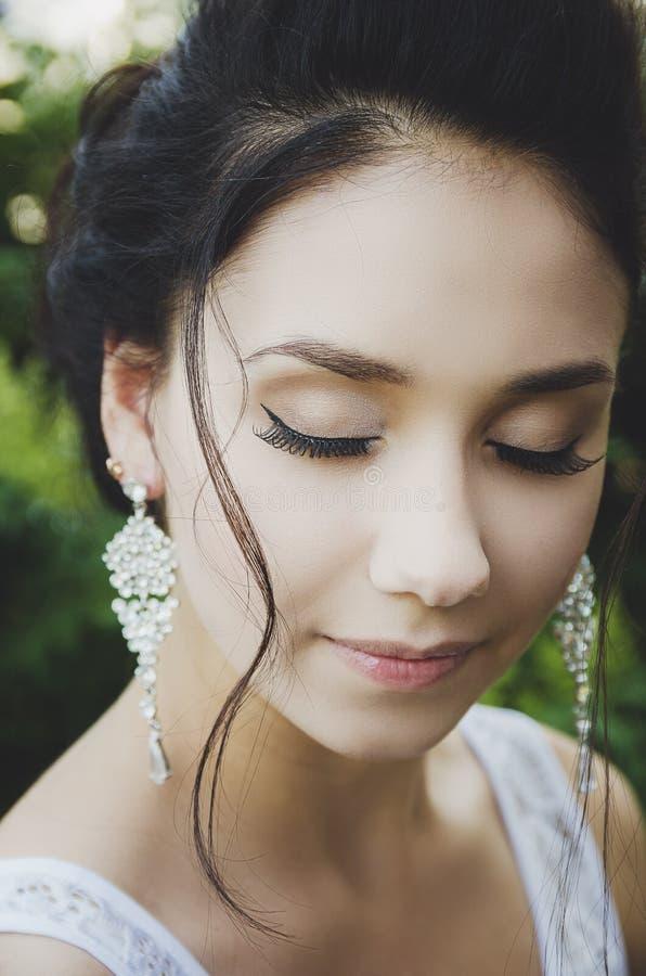Portrait of a beautiful brunette girl with closed eyes, makeup, false eyelashes stock photography