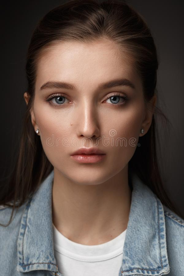 Portrait of beautiful brunette girl with hair tied back dressed in jeans jacket on the dark background in the studio stock photos