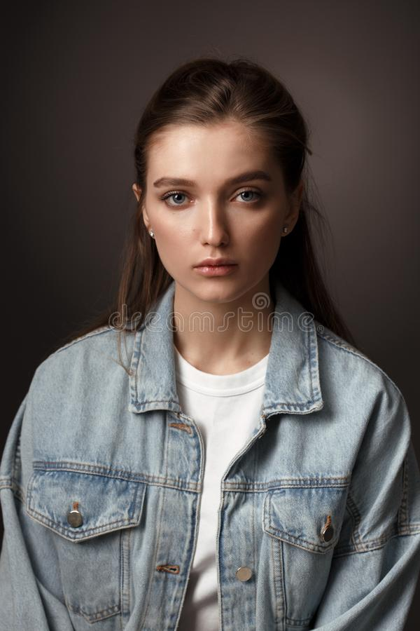 Portrait of beautiful brunette girl with hair tied back dressed in jeans jacket on the dark background in the studio royalty free stock photo