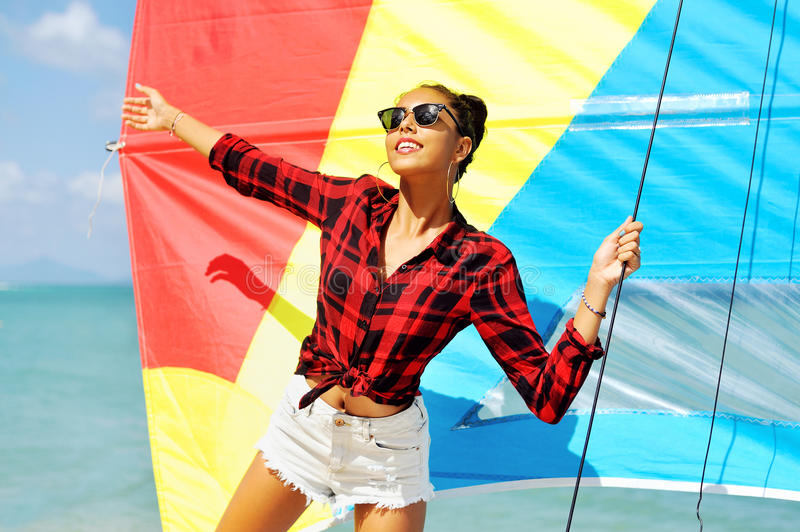 Portrait of beautiful brunette girl holds boat sails and smiling.  royalty free stock photography