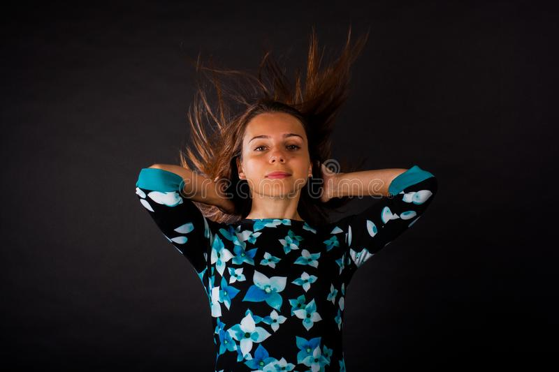 The girl with developing long hair on black background stock photography