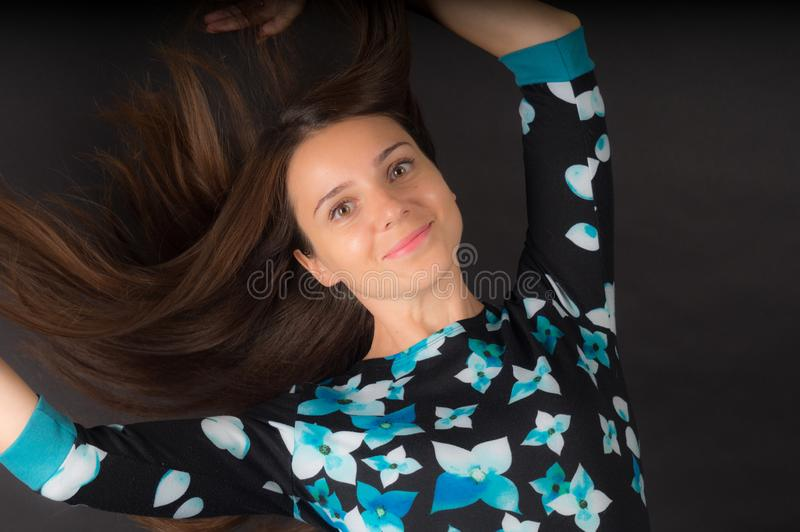 The girl with developing long hair on black background stock image