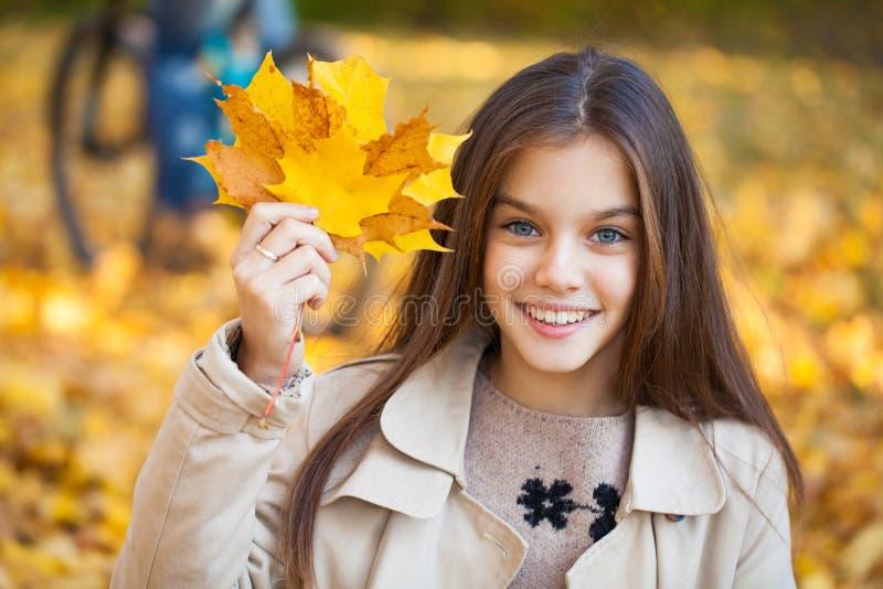 Portrait of a beautiful brunette little girl, autumn park outdoors royalty free stock photos