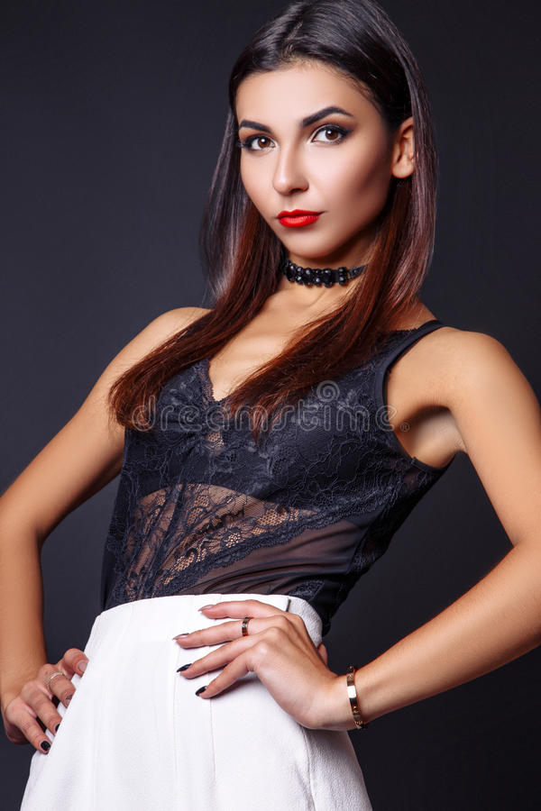 Portrait of beautiful brunette woman in a black blouse and white pants,. Fashion photo shot. royalty free stock photography