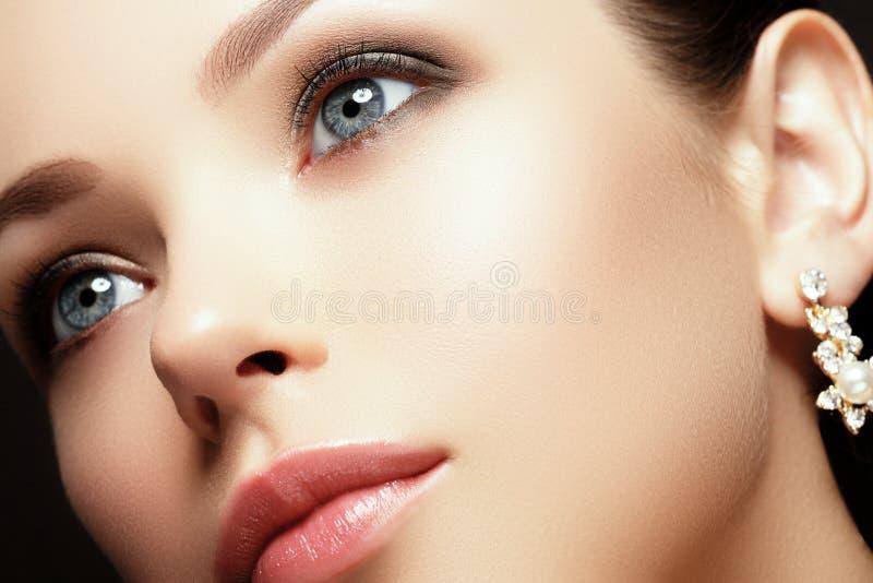 Portrait of beautiful brunette woman. Fashion portrait of beautiful luxury woman with jewelry royalty free stock photography