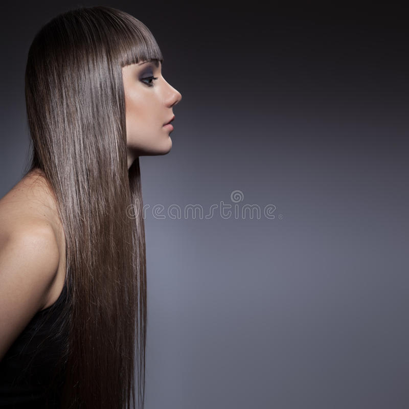 Portrait of a beautiful brunette woman with long straight hair royalty free stock image