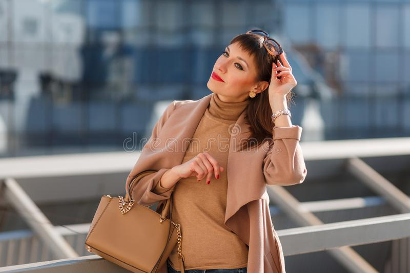 Portrait of beautiful brunette young woman in nice brown beige coat, denim jeans and sunglasses. Genuine leather bag, high heels stock photo