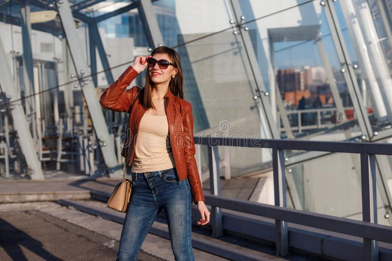 Portrait of beautiful brunette young woman in nice red brown jacket, denim jeans and sunglasses. Genuine leather bag, high heels royalty free stock photo