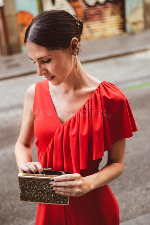 Portrait of beautiful brunette young woman with topknot hairstyle wearing red ruffles dress looking in the purse. Fashion photo. Portrait of beautiful brunette royalty free stock photos